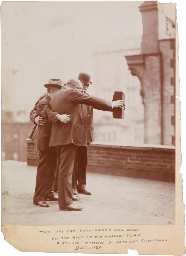 A black and white photo of the Five Men (1920) taking a selfie with an old fashioned camera