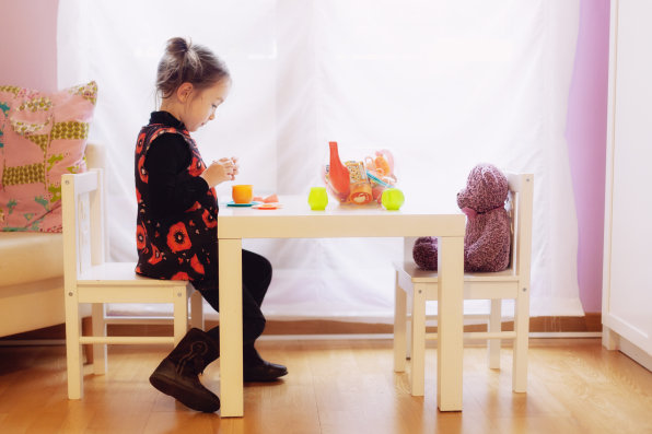 little girl make a tea party with her plush teddy bear
